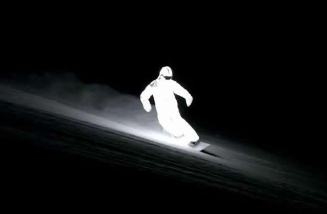 Un snowboardeur nocturne couvert de LED illumine les pentes enneigées