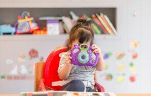 Un bébé joue dans sa chaise haute